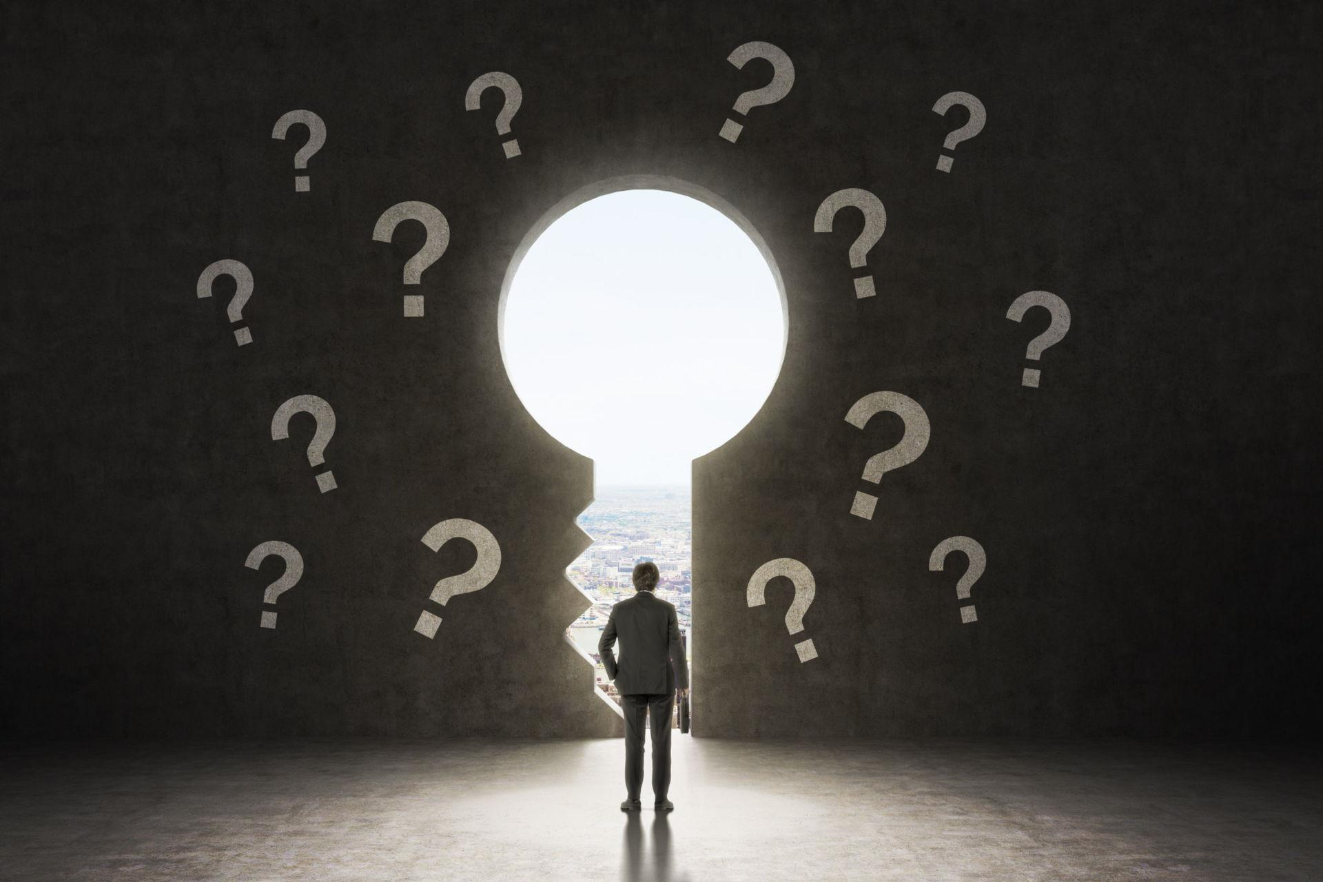 Business Man Looking Through A Large Key Hole Surrounded With Question Marks