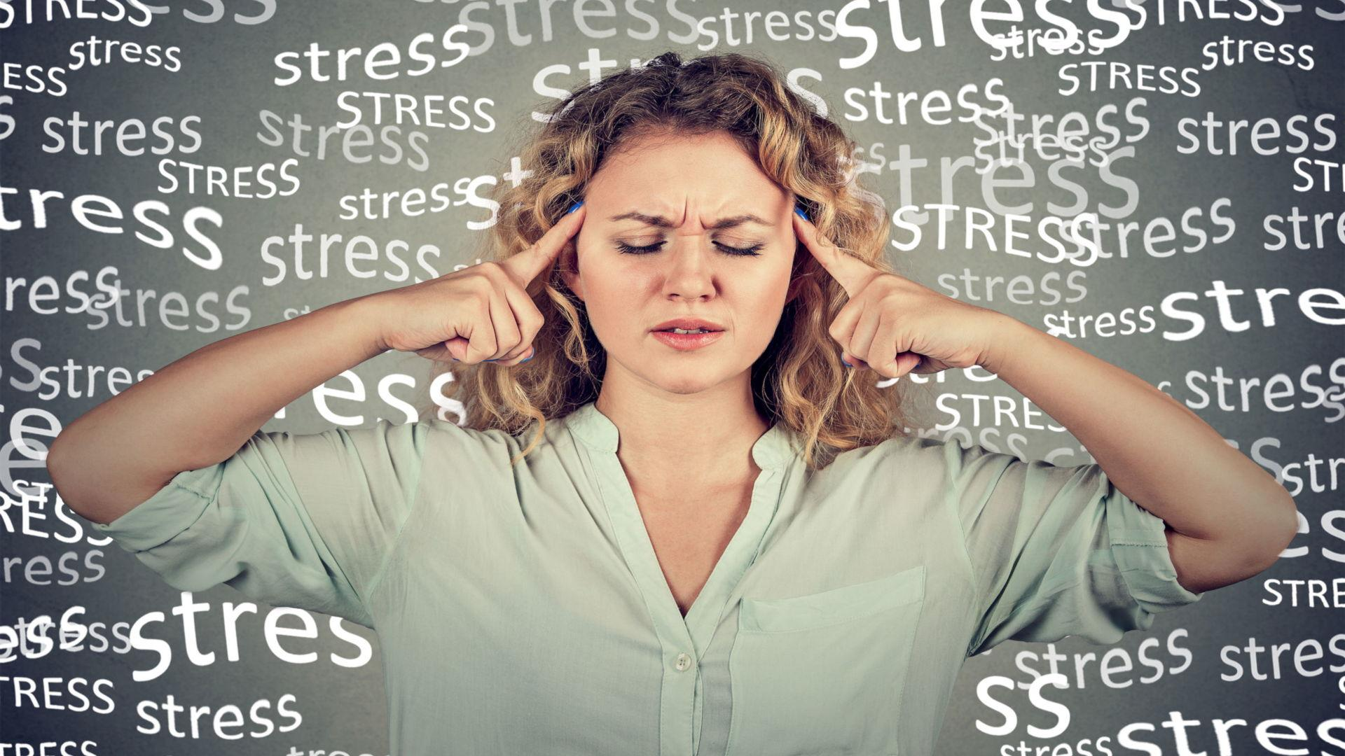 oung Woman Looking Stressed With The Word Stress Written Behind Her